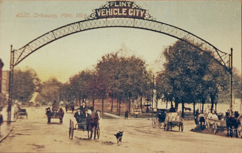 This is the northern most arch. Ahead is McFarlan Park. Detroit St.  is to the left, and Saginaw St. is veering off to the right. Date of photo unknown.